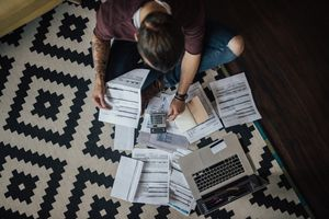 A top view of a person sitting on the floor surrounded by their credit card bills and a laptop, deciding between a balance transfer and a debt consolidation loan