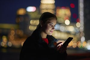 a woman checking her phone with a cityscape background at night