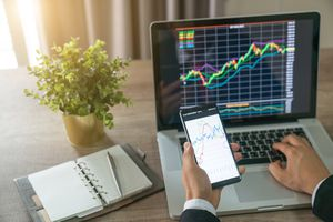 Investor analyzing stock market investments with financial dashboard, business intelligence (BI), and key performance indicators (KPI) on smartphone and computer screens.