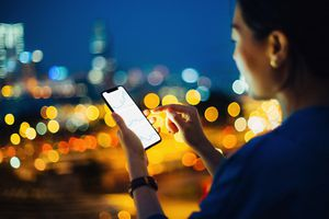 Businesswoman checking stock market data on mobile phone in city at night.