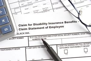 A disability insurance claim form with pen, calculator, and eyeglasses.