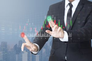 A businessman trading stocks on a digital screen.