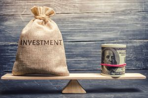 A money bag with the word Investments and dollars on a scale.