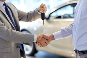 Close up of dealer giving key to new owner and shaking hands in auto show.