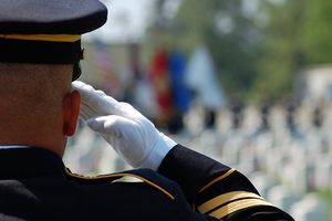 Man in military uniform salutes in front of graves in a cemetery.