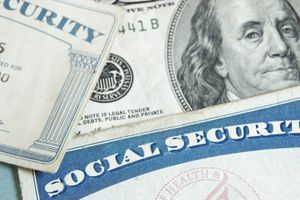 Social security cards angled on top one hundred dollar bill.