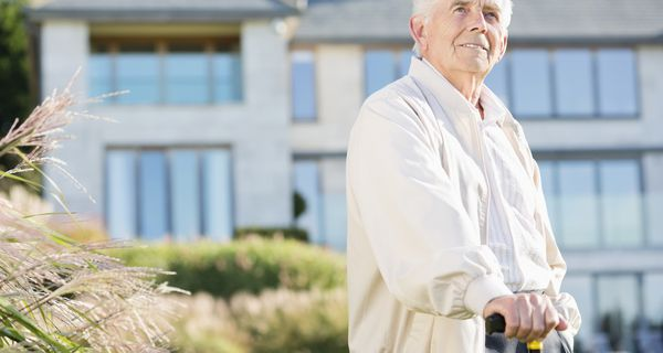 Man in windbreaker, holding cane, stands outdoors in front of retirement community building.
