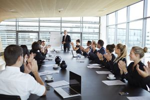 business people clapping in a board room meeting at a presentation