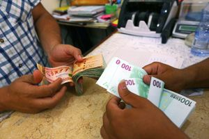 Close up of hands exchanging bank notes at a currency exchange in Tripoli
