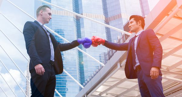 Business Colleagues With Boxing Gloves Standing Against Buildings in City