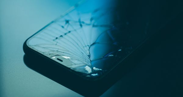 Close-Up Of Cracked Mobile Phone On Table