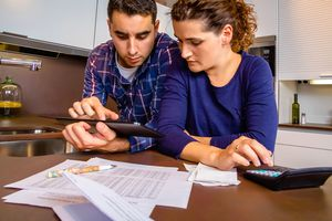 Worried young couple at kitchen table with papers and calculator