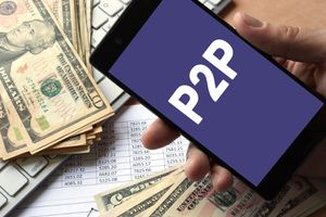 Smartphone in Hand With P2P. Peer to Peer Lending Concept