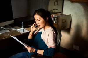 Portrait of Korean woman on cell phone reading important document.