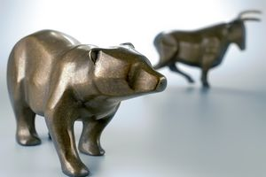 A metal sculpture of a bear and bull representing the stock market, with the bear in the foreground.