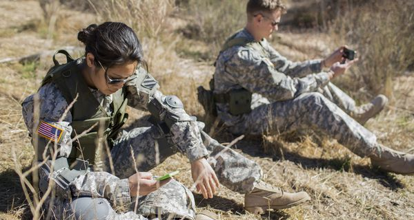 Two active-duty military members using their phones in the field.