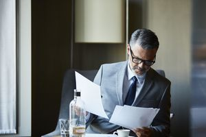 man in a suit looking at papers while at a table with water and espresso in front of him
