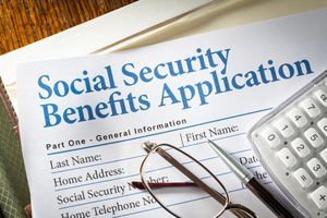 A Social Security Benefits form with pen, glasses, and calculator.