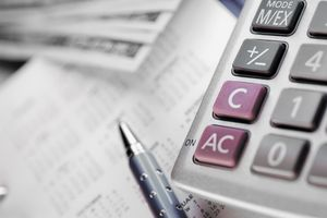 Close-up of a calculator and a pen on a calendar