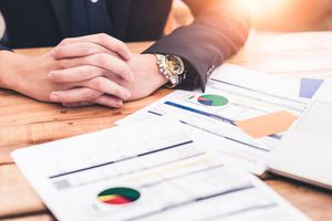 An image of the both hands of businessman and business chart document on the wooden table during sunrise.