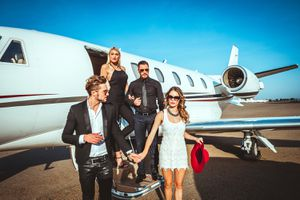 Two Wealthy Couples Exiting a Parked Private Jet Parked on an Airport Tarmac