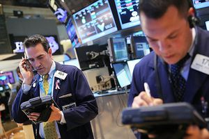 Two men on the trading floor work to buy and sell securities with multiple computer screens behind them.