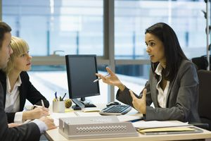 Financial advisor meets with clients in an office