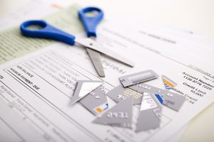A pair of scissors and a cut-up credit card on a credit card bill.