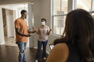 An African American couple tour for a house with a real estate agent during the COVID-19 pandemic
