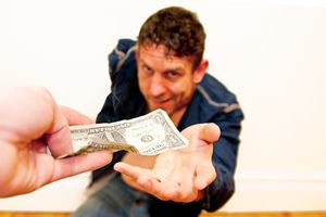 A man grinning broadly as he takes a dollar