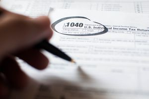 A young person writing on a tax document