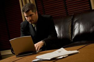 Man in suit, seated on black leather couch, works on a laptop.