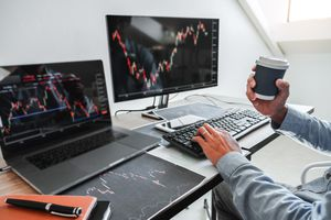 An investor reviews stock charts on a laptop and monitor.