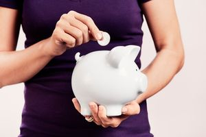 Woman adds coin to piggy bank