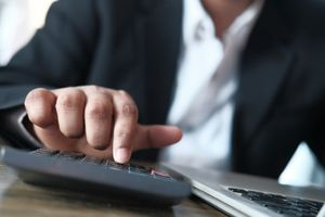 A businessman hand using calculator for calculating cost.