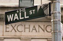 Wall St. sign on streetlight pole in front of the stock exchange in New York City.