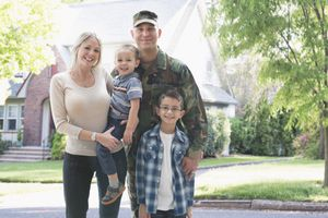 Military family in front of house