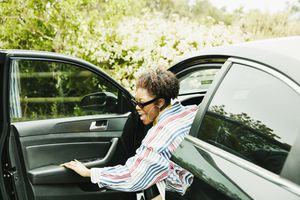 Smiling woman stepping out of drivers seat after parking car