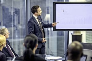 Financial analyst standing next to a monitor with graphs and explaining them to company board.