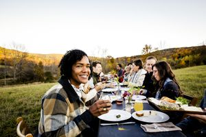 People having dinner at a long table outside in a field