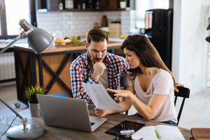 Couple Checking Bills at Home Using Laptop