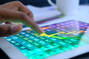 Close-up of a hand touching a tablet screen to analyze a stock market chart
