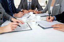 Five businesspeople sit at a meeting table to go over contracts