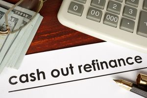 Paper with words cash out refinance on a wooden background.