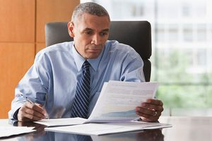 Executor of estate sitting at desk with papers