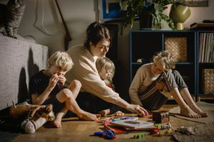 A mom sits on the floor with three kids, surrounded by toys and books.
