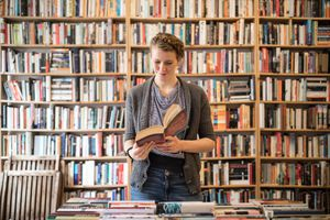 Woman reading book in front of a full bookshelf