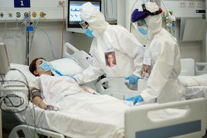 Masked woman on ventilator, with two medical workers in full pandemic PPE