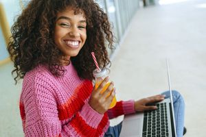 Smiling woman with laptop and juice