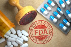 FDA Approved Concept. Rubber Stamp With FDA and Pills on Craft Paper